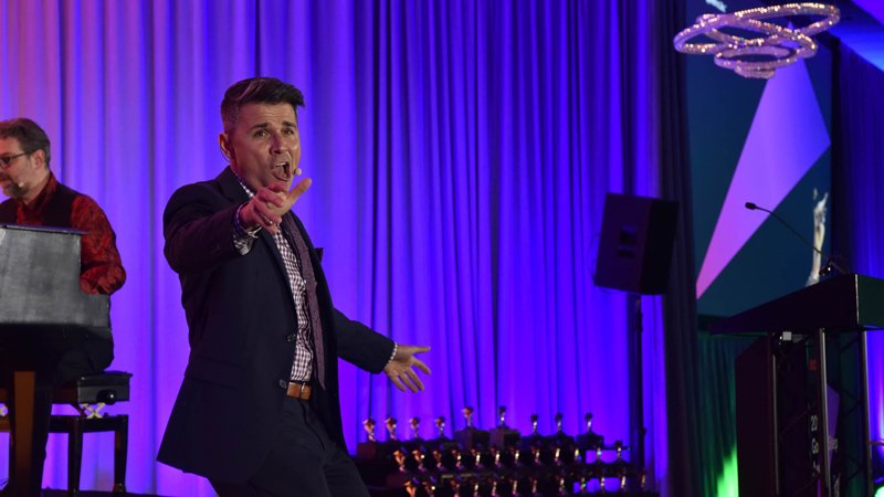 Man with microphone engaging audience at awards event