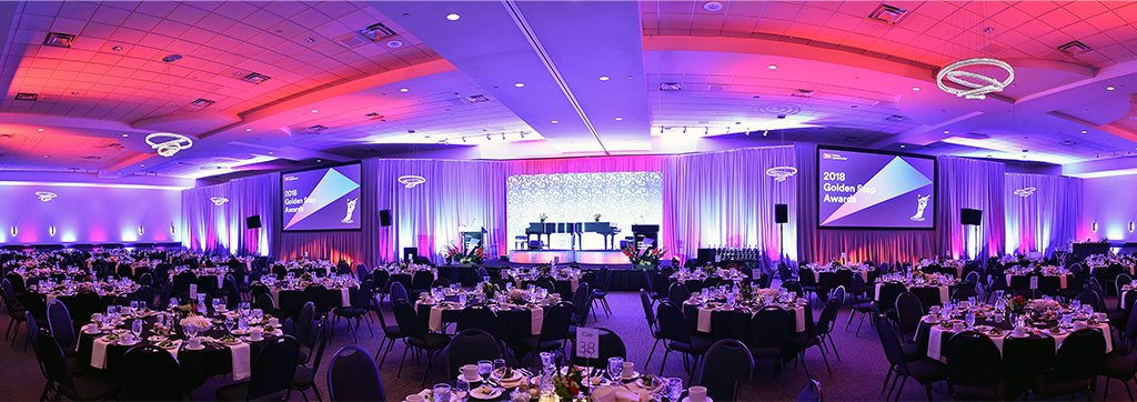 Panoramic view of Live Corporate Awards Gala state with pink and purple and many tables